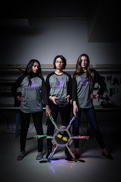 Three female students stand side by side. The one in the middle is holding the controls of a drone, the other two are holding the arms of the drone.