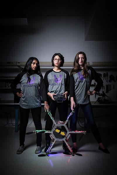 Trois étudiantes sont debout l'une à côté de l'autre. Celle au milieu tient les commandes d'un drone, les deux autres tiennent les bouts du drone.
